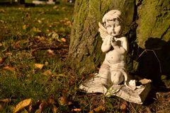Kneeling praying old cherub statute Stock Photography