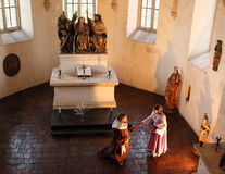 Kneeling Priest in Chapel. Priest kneeling in front of a woman in the chapel as a summer 2015 performance at Svihov Water Castle, Western Bohemia Royalty Free Stock Photo