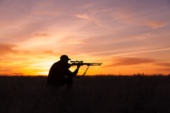 Kneeling Rifle Hunter Shooting in Sunset. A rifle hunter silhoutted against a dramatic sunset with rifle shouldered while kneeling Stock Photography