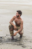 Kneeling Shirtless Soldier on the Beach Sand Royalty Free Stock Photo