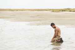 Kneeling Shirtless Soldier at the Sea Water. Muscled Shirtless Soldier in Camouflage Pants and Black Shoes Kneeling at the sea water Royalty Free Stock Photo