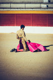 Kneeling torero awaiting for the bull. An kneeling bullfighter awaiting for the bull in the bullring. Corrida de toros Royalty Free Stock Photos