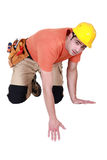 Kneeling tradesman reaching down Royalty Free Stock Image