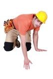 Kneeling tradesman reaching down. For something Royalty Free Stock Image