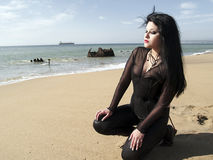 Kneeling woman on the sand Royalty Free Stock Image