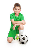 Kneeling young soccer player with football Stock Photo