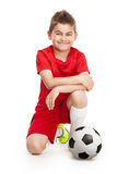 Kneeling young soccer player with football Royalty Free Stock Photography