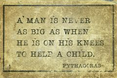 On knees Pyth. A man is never as big as when he is on his knees - ancient Greek philosopher Pythagoras quote printed on grunge vintage cardboard Stock Photos