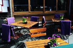 Kneipen-Terrasse im Freien mit purpurroten Blumen Stockbild