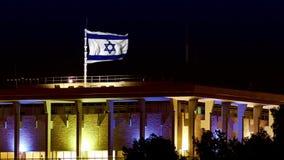 Knesset con il volo e la bandiera d'ondeggiamento di Israele alla notte stock footage