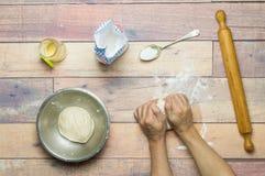 Kneten des Teigs für das Kochen auf Holztisch Stockfoto