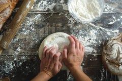 Knetender Brotteig der Frau mit ihren Händen stockfotografie