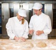 Knetender Brotteig des Lehrer- und Bäckerlehrlings Stockbilder