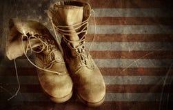 Kängor för USA-armé på den gamla pappers- flaggabakgrunden Royaltyfri Fotografi
