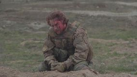 Kniaź raniący żołnierz siedzi na ziemi Strzelający na Kinowej kamerze w 4K UHD zdjęcie wideo