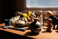 Knick-knacks on a Shelf. An image of old dusty knick-knacks on a shelf.  They include a bell, a baby, a key, a bronze shoe, a unicorn, and a mammoth Royalty Free Stock Images