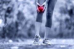 Knie-Verletzung - Sport, der Knieverletzungen auf Frau laufen lässt stockfotografie