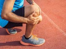 Knie-Verletzungen tragen Sie Mann mit den starken athletischen Beinen zur Schau, die Knie halten stockbild