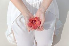 Knielende vrouw die in witte kleding een tropische bloem in haar hand houden royalty-vrije stock afbeelding