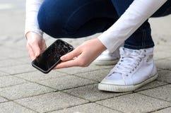 Kniende Person, die oben gebrochenes Telefon auf Straße auswählt Lizenzfreie Stockfotos