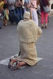 Kniender Pilger in Assisi - Gebet und Abzahlung eines Sünders Lizenzfreies Stockfoto