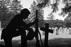 Kniender Soldat nahe bei dem Kampf-Kreuz eines gefallenen Kameraden nahe Grabsteinen I Stockfotografie