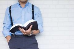 Kniestück, schließen herauf Mann im blauen Hemdholdingschwarzbuch der Bibel, buddhistisch, katholisch, christlich, Gebet auf Wand lizenzfreie stockfotos
