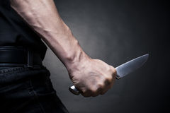 Knife. In a hand.Background black Royalty Free Stock Images