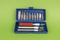Knife for accurate work with replaceable blades on a green background, there is a place to fill royalty free stock photo