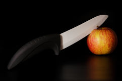 Knife and apple. Ceramic knife cuts the apple stock photography