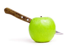 Knife in the apple over white background Royalty Free Stock Photography