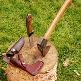 Knife and axe on log. Knife and axe displayed on a tree trunk Royalty Free Stock Images