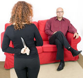 From knife for backs woman, man in background Royalty Free Stock Images