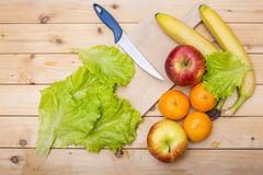 Knife, banana, apples, salad leaves, tangerine and a wooden cutting plate on a wooden background Stock Photo