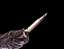 Knife in black glove Stock Images