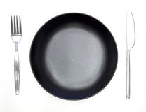 Knife, black plate and fork Stock Images