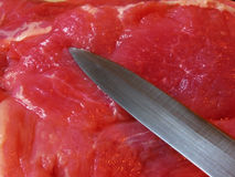Knife blade on meat. Knife ready to cut raw pork Stock Photos