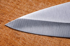 Knife blade on an old chopping board Royalty Free Stock Image