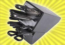 Knife block / knives. Knives in a knife block. Yellow starburst background stock photography