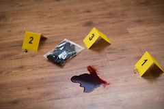 Knife in blood and evidence marker at crime scene. Murder, kill and forensic concept - knife in blood and evidence marker at crime scene stock photos
