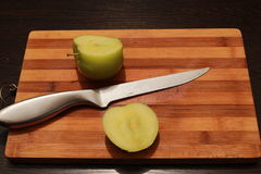 Knife on the board and two halves of the apple. A green apple is cut into two parts royalty free stock photo