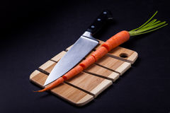 Knife with carrot and wooden cutting board Royalty Free Stock Photo