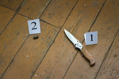 Knife and cartridge case on a brown wooden background, murder, robbery, evidence on the floor, investigation stock image
