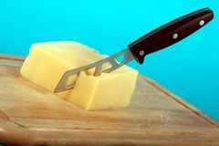 Knife in Cheese. Cheese and knife on the plate royalty free stock photo