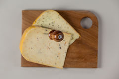Knife on cheese slice on wooden board Stock Photo