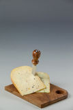 Knife on cheese slices on wooden board Royalty Free Stock Image
