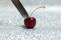 Knife on Cherry. On silver glitter background royalty free stock photos
