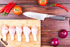 Knife, chicken legs and vegetables on an. Old table: tomatoes, cucumbers, pepper, onions, lettuce leaves Royalty Free Stock Photo