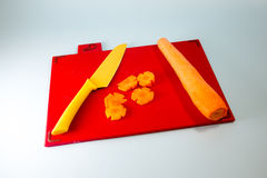 Knife And Chopped Carrot. A yellow knife and chopped carrot on a chopping board stock photo
