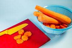 Knife And Chopped Carrot. A yellow knife and chopped carrot on a chopping board royalty free stock photo